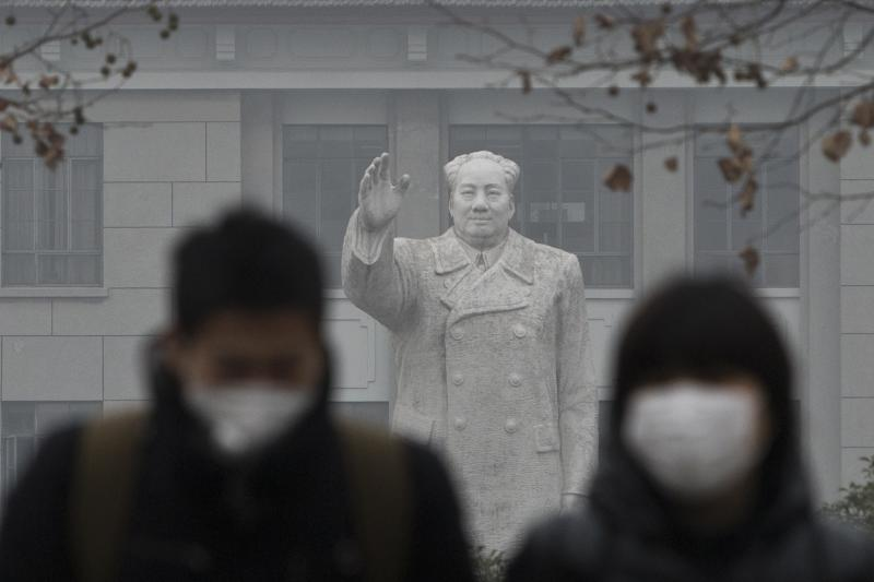 People wearing masks walk in front of the statue of late Chinese leader Mao Zedong in a university, during a hazy day in downtown Shanghai