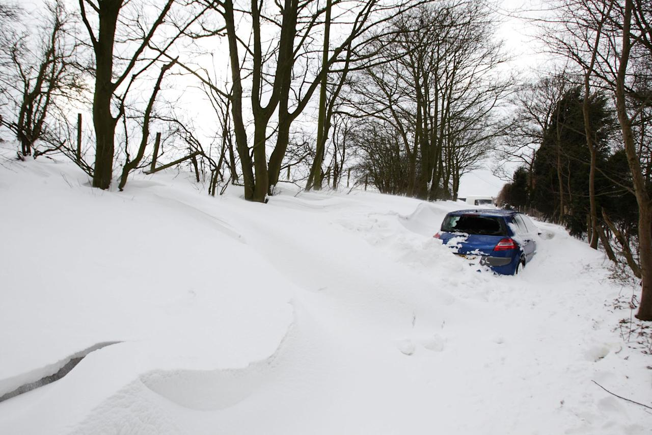 A stranded vehicle near Barr Beacon in the West Midlands is almost covered by snow (SWNS)