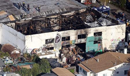 FILE PHOTO:    Recovery teams examine the charred remains of the two-story converted warehouse that caught fire killing dozens in Oakland, California, U.S., December 4, 2016. REUTERS/Lucy Nicholson/File Photo
