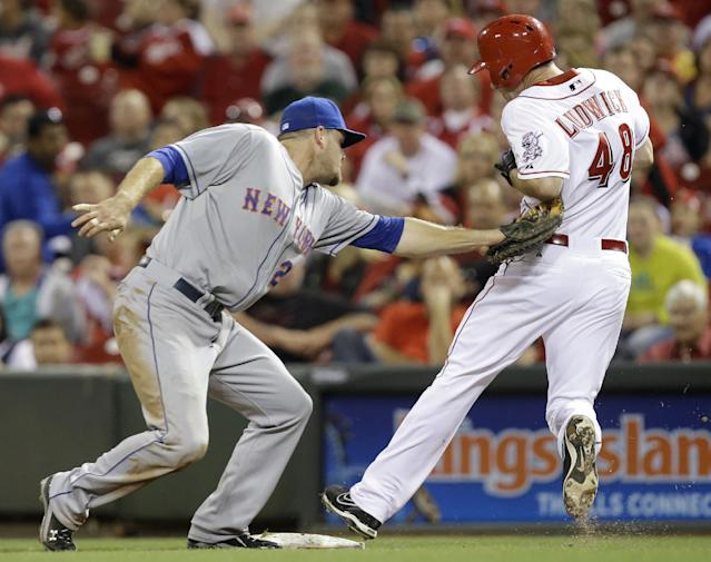 New York Mets first baseman Lucas Duda tags out Cincinnati Reds' Ryan Ludwick (48) at first base after Duda was pulled off the bag by a high throw in the eighth inning of a baseball game, Tuesday, Sept. 24, 2013, in Cincinnati. New York Mets won 4-2. (AP Photo/Al Behrman)