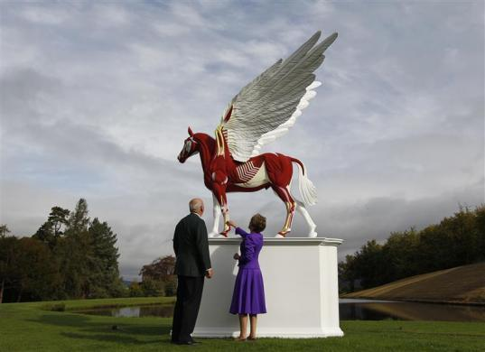 The Duke and Duchess of Devonshire view the sculpture Legend by Damien Hirst in the gardens of their home Chatsworth House in central England September 9, 2011.