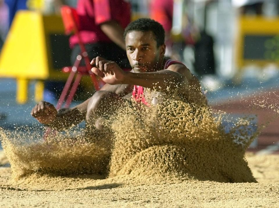 Cuba's Ivan Pedroso lands in the sand during the men's long jump qualification round at the World Athletics Championships in Seville 26 August 1999. (ELECTRONIC IMAGE) (Photo by Eric Feferberg / AFP) (Photo by ERIC FEFERBERG/AFP via Getty Images)