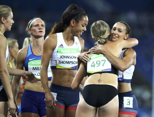 2016 Rio Olympics - Athletics - Women's Heptathlon 800m - Olympic Stadium - Rio de Janeiro, Brazil - 13/08/2016. Brianne Theisen-Eaton (CAN) of Canada (497) hugs Jessica Ennis-Hill (GBR) of Britain (R) as Katarina Johnson-Thompson (GBR) of Britain (C) looks on. REUTERS/Lucy Nicholson FOR EDITORIAL USE ONLY. NOT FOR SALE FOR MARKETING OR ADVERTISING CAMPAIGNS.