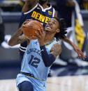 Memphis Grizzlies guard Ja Morant, right, drives to the rim past Denver Nuggets forward Will Barton, left, in the first half of an NBA basketball game Monday, April 19, 2021, in Denver. (AP Photo/David Zalubowski)