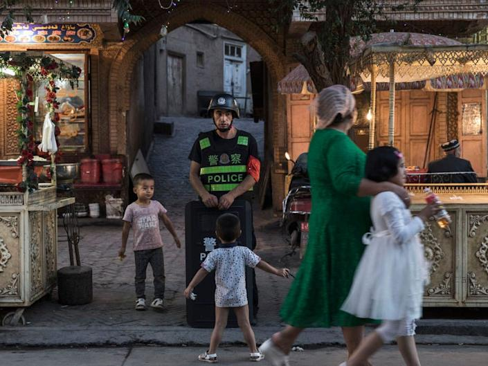 A police officer in Xinjiang watches over the population in Kashgar.