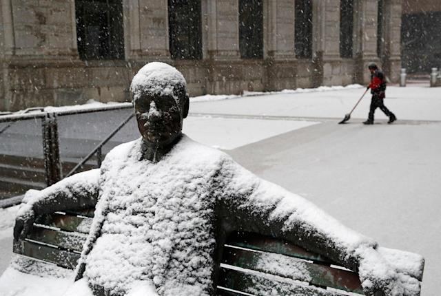 <p>Snow sticks to a statue of a man sitting on a park bench as a worker shovels a light snowfall Wednesday, March 21, 2018, in Baltimore. A spring nor'easter targeted the Northeast on Wednesday with strong winds and a foot or more of snow expected in some parts of the region. (Photo: Patrick Semansky/AP) </p>
