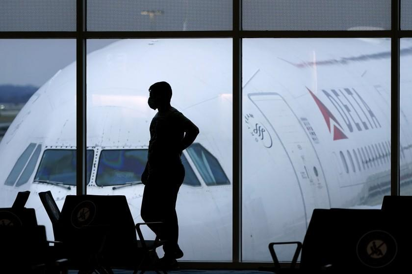 A passenger wears a face mask to help prevent the spread of the new coronavirus as he waits for a Delta Airlines flight at Hartsfield-Jackson International Airport in Atlanta, Thursday, Feb. 18, 2021. (AP Photo/Charlie Riedel)