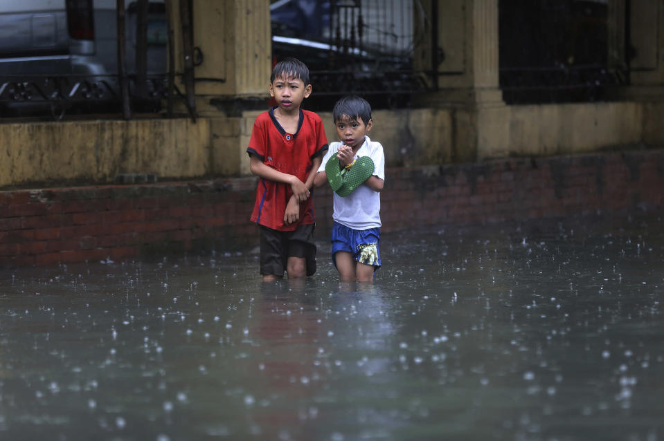 <p>Filipino boys stand along a flooded road in suburban Mandaluyong, east of Manila, Philippines, as monsoon downpours intensify while Typhoon Nepartak exits the country on Friday, July 8, 2016. (AP Photo/Aaron Favila) </p>
