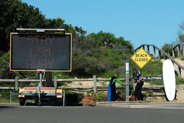 People shower at Freshwater beach following its closure on Sunday.