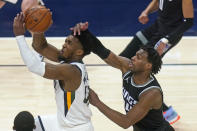 Utah Jazz guard Donovan Mitchell, left, goes to the basket as Sacramento Kings guard Buddy Hield, right, defends in the second half during an NBA basketball game Saturday, April 10, 2021, in Salt Lake City. (AP Photo/Rick Bowmer)