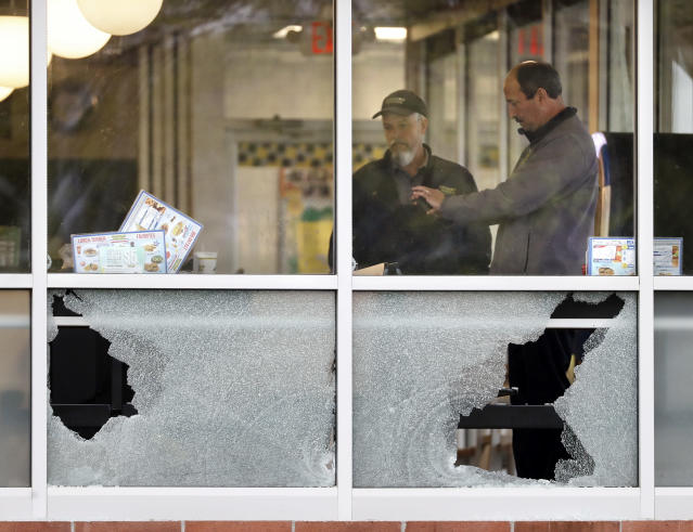 <p>People look over an area near a window shot out at a Waffle House restaurant Sunday, April 22, 2018, in Nashville, Tenn. Several people died after a gunman opened fire at the restaurant early Sunday. (Photo: Mark Humphrey/AP) </p>