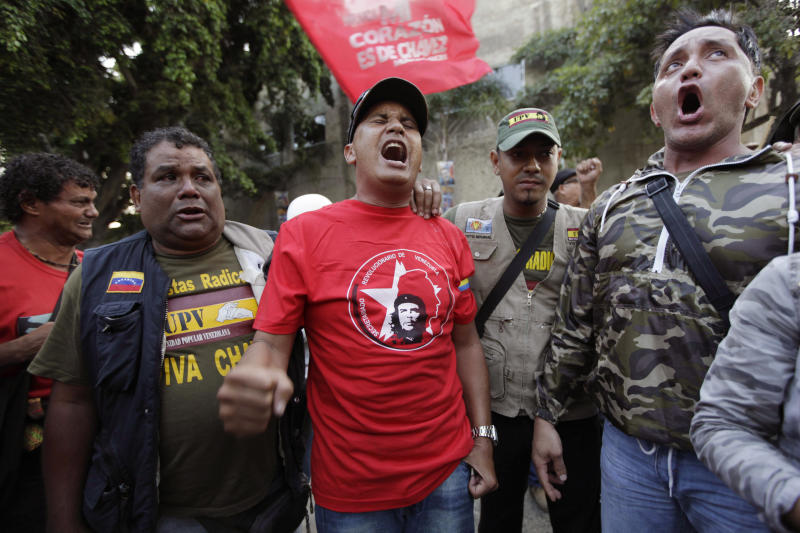 "Supporters of Venezuela's President Hugo Chavez yell ""Long Live Chavez!"" and sing their nation's anthem after learning that Chavez has died through an announcement by the vice president in Caracas, Venezuela, Tuesday, March 5, 2013. Venezuela's Vice President Nicolas Maduro announced that Chavez died on Tuesday at age 58 after a nearly two-year bout with cancer. During more than 14 years in office, Chavez routinely challenged the status quo at home and internationally. He polarized Venezuelans with his confrontational and domineering style, yet was also a masterful communicator and strategist who tapped into Venezuelan nationalism to win broad support, particularly among the poor. (AP Photo/Ariana Cubillos)"