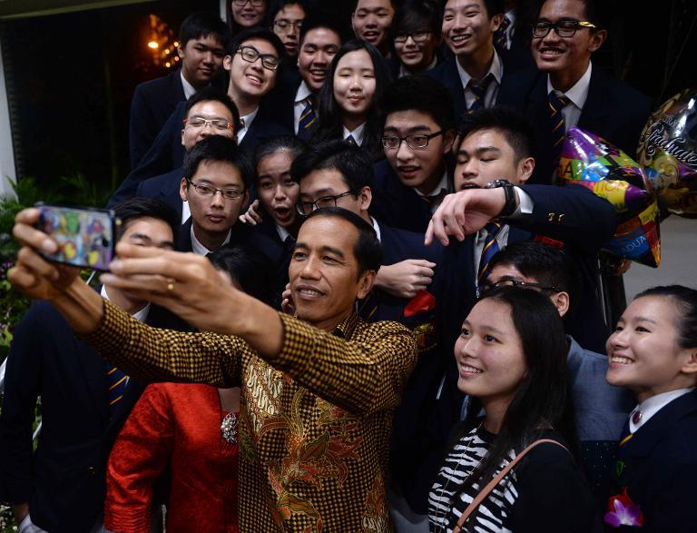 Indonesian President Joko Widodo takes a selfie with classmates of his youngest son Kaesang Pangarep at the Anglo-Chinese International School in Singapore on November 21, 2014
