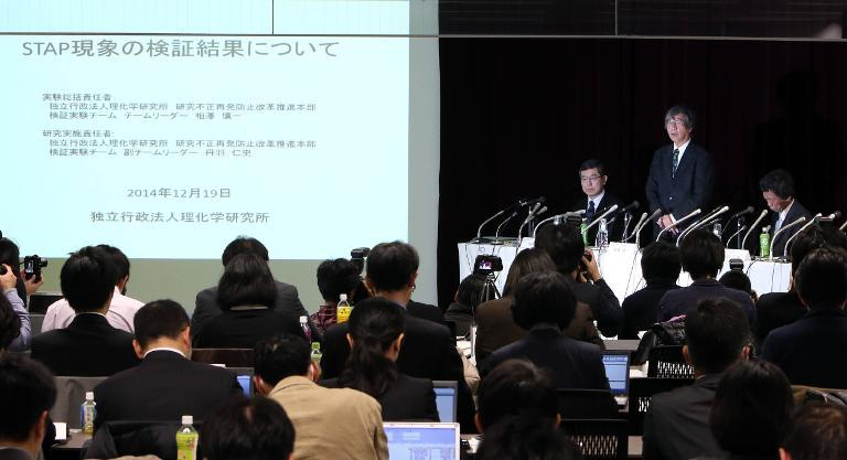 The government-backed Riken Institute verification experiment team leader Shinichi Aizawa (right C, standing) tells journalists in Tokyo on December 19, 2014, that a so-called ground breaking study on stem cells cannot be reproduced