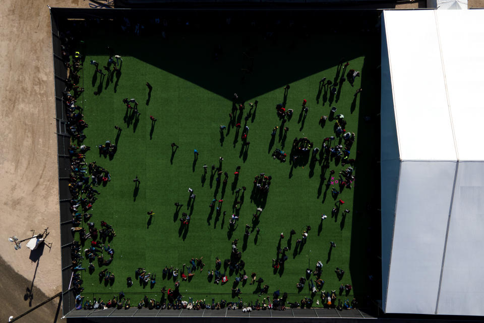 FILE - In this Friday, March 19, 2021, photo migrants are seen in a green area outside of a soft-sided detention center after they were taken into custody while trying to sneak into the U.S. in Donna, Texas. The Biden administration is facing growing questions about why it wasn't more prepared for an influx of migrants at the southern border. The administration is scrambling to build up capacity to care for 14,000 young undocumented migrants now in federal custody — and more likely on the way. (AP Photo/Julio Cortez, File)