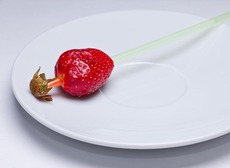Hulled strawberry with a straw through it on a plate.