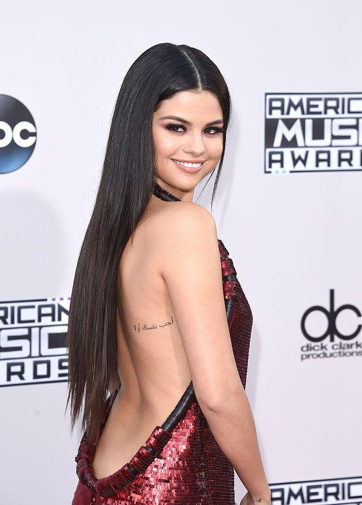 """<p>Bang Bang also etched a phrase in Arabic onto Gomez's back in 2014 which translates to 'Love Yourself First'. The tattoo artist explained to <a href=""""https://www.eonline.com/news/560392/selena-gomez-gets-a-new-tattoo-see-pics-and-find-out-the-meaning"""" rel=""""nofollow noopener"""" target=""""_blank"""" data-ylk=""""slk:E! News"""" class=""""link rapid-noclick-resp"""">E! News </a>at the time: 'Selena already had it written out how she wanted. The tattoo is about 4 inches, and didn't take too long, probably about 30-45 minutes. The longest part is laying it out. We played with it a bit laying it out, until we found the perfect spot.'</p>"""