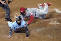 Minnesota Twins' Marwin Gonzalez, left, scores on a wild pitch by Cincinnati Reds' Luis Castillo, right, who covers the plate during the fourth inning of a baseball game Saturday, Sept. 26, 2020, in Minneapolis. The Twins won 7-3, with Castillo taking the loss. (AP Photo/Jim Mone)