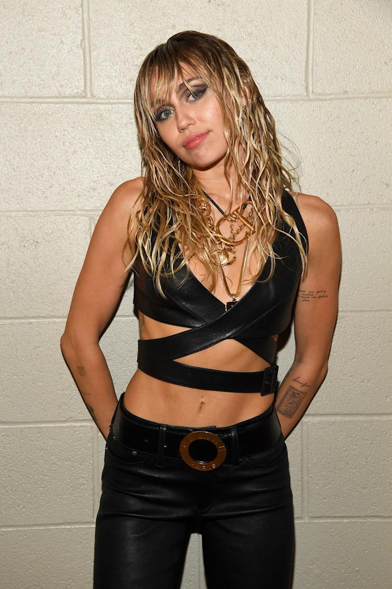 Miley Cyrus stands in front of a white wall with her hands behind her back. She is wearing a black crop top and pants