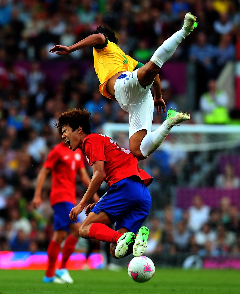 MANCHESTER, ENGLAND - AUGUST 07: Kim Hyunsung of Korea clashes with Alex Sandro of Brazil during the Men's Football Semi Final match between Korea and Brazil, on Day 11 of the London 2012 Olympic Games at Old Trafford on August 7, 2012 in Manchester, England. (Photo by Stanley Chou/Getty Images)
