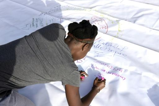 A volunteer signs a poster