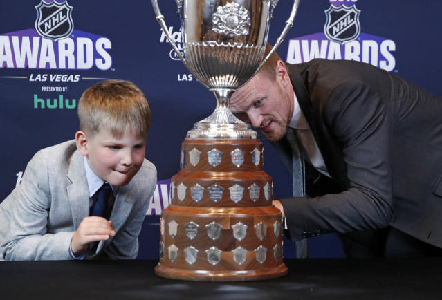 Henrik Sedin, right, looks at King Clancy Memorial Trophy with his son Harry after winning the award at the NHL Awards, Wednesday, June 20, 2018, in Las Vegas. (AP Photo/John Locher)