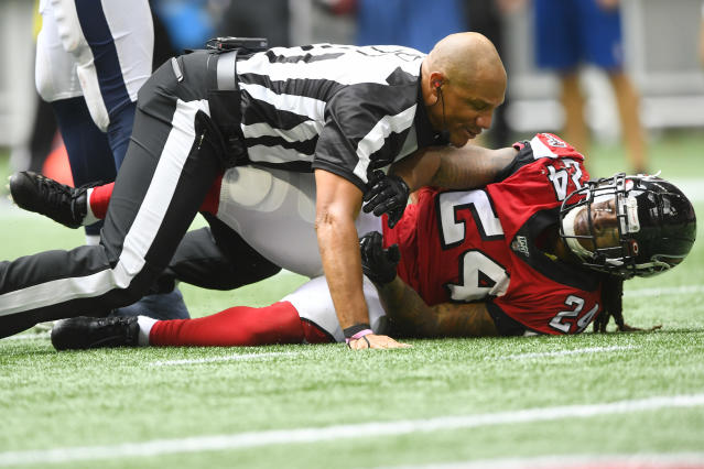 A referee had to wrestle the Falcons' Devonta Freeman to the ground after he got into a heated altercation with the Rams' Aaron Donald. (AP Photo/John Amis)