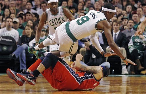 Boston Celtics guard Rajon Rondo, top, collides with New Jersey Nets guard Deron Williams, bottom, during the second quarter of an NBA basketball game in Boston, Friday, March 2, 2012. (AP Photo/Charles Krupa)