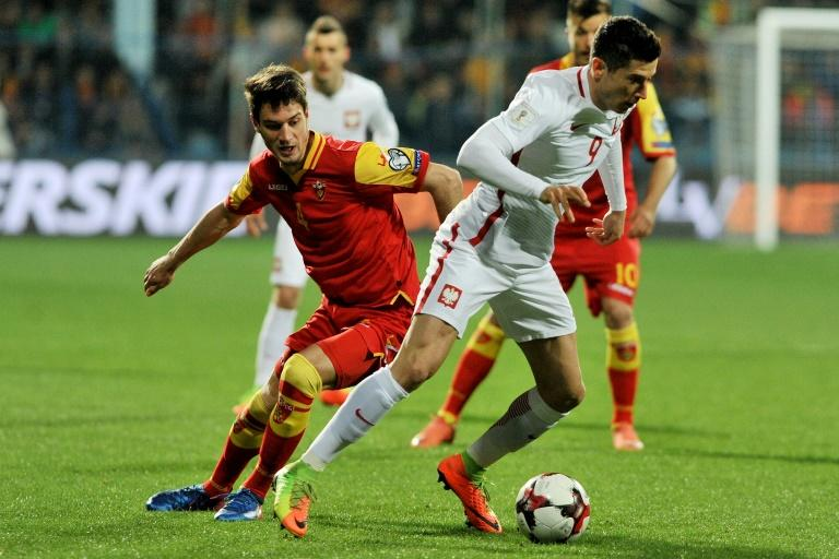 Poland's Robert Lewandowski (R) fights for the ball with Montenegro's Nikola Vukcevic during their FIFA World Cup 2018 qualification match, in Podgorica, on March 26, 2017