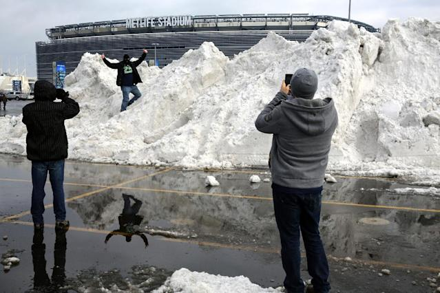 A person poses for photos on a mound of snow on the parking lot of MetLife Stadium before an NFL football game between the Seattle Seahawks and the New York Giants, Sunday, Dec. 15, 2013, in East Rutherford, N.J. (AP Photo/Peter Morgan)