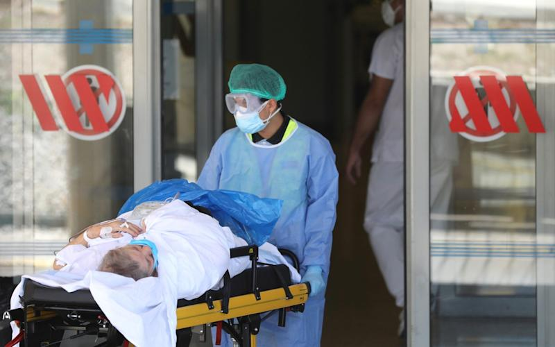 A person is carried on a stretcher at Arnau de Vilanova hospital, after Catalonia's government imposed new restrictions