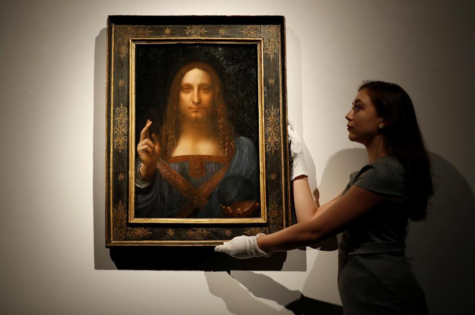 <p>A member of Christie's staff with the Salvator Mundi</p> (Reuters)