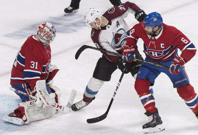 Colorado Avalanche's Nathan MacKinnon (29) moves in on Montreal Canadiens goaltender Carey Price as Canadiens' Shea Weber (6) defends during the second period of an NHL hockey game Saturday, Jan. 12, 2019, in Montreal. (Graham Hughes/The Canadian Press via AP)