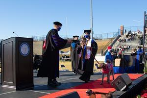 """Maggie and Mona Leptrone cross the stage, receiving Mona's honorary """"dog-ree"""" from UWG President Dr. Brendan B. Kelly. Mona was the first canine companion in university history to receive an honorary degree."""