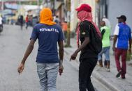 A demonstrator walks with a knife in his hand during a protest to demand the resignation of Haiti's president Jovenel Moise on the 216th anniversary of Battle of Vertieres in Port-au-Prince, Haiti, Monday, Nov. 18, 2019. At least four people were shot and wounded during a small protest in Haiti's capital after a speech by embattled President Moise. A local journalist, a police officer and two protesters were rushed away with apparent bullet wounds. (AP Photo/Dieu Nalio Chery)