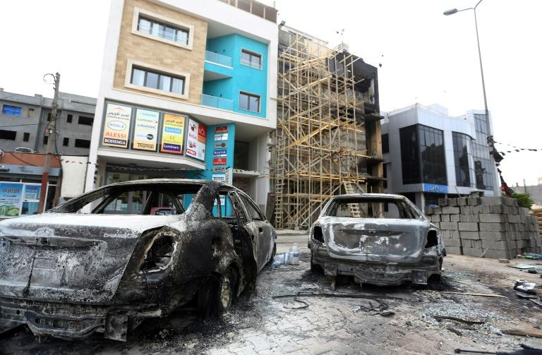 Charred vehicles sit outside the Tripoli offices of Al-Nabaa TV on March 15, 2017 amid an intense battle for the capital