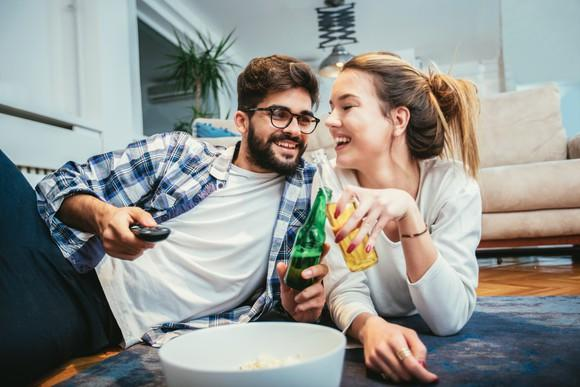 Couple drinking beer while lounging on the floor with a bowl of popcorn between them.