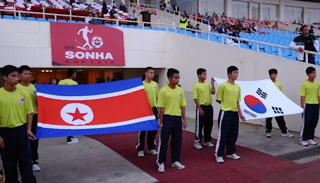 Flags of North Korea (L) and South Korea are carried prior to a football match between the two countries' U-23 teams during the Vietnam Football (VFF) Federation Son Ha Cup tournament on November 4, 2010 (AFP Photo/HOANG DINH NAM)