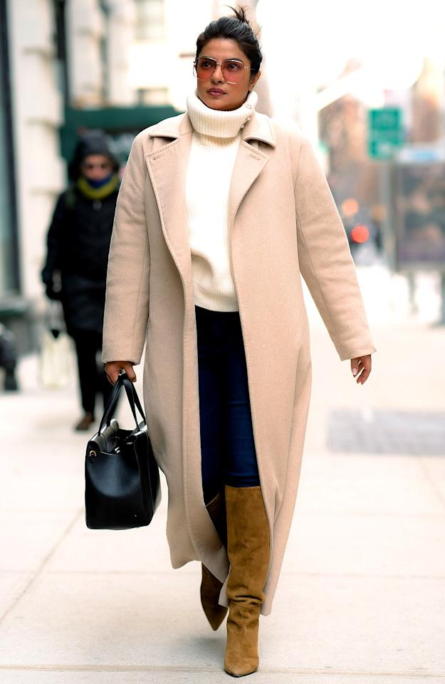 wears a cream turtleneck sweater, a beige wool overcoat, dark wash skinny jeans, brown suede knee-high boots and a black structured handbag in N.Y.C.
