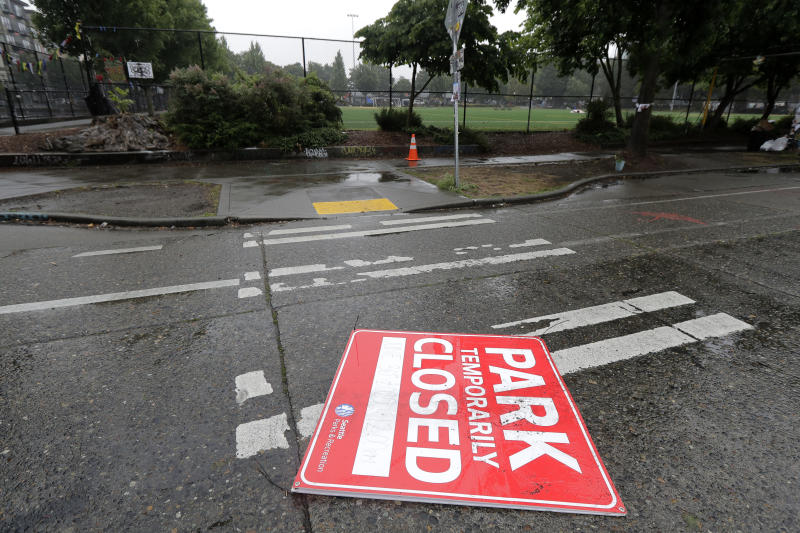 A sign that indicates Cal Anderson Park will be closed at noon lies in the street, Tuesday, June 30, 2020 at the CHOP (Capitol Hill Occupied Protest) zone in Seattle. Earlier in the day, workers removed concrete barricades at one intersection, but protesters quickly moved couches, trash cans and other materials to replace the barricades. The area has been occupied by protesters since Seattle Police pulled back from their East Precinct building following violent clashes with demonstrators earlier in the month. (AP Photo/Ted S. Warren)