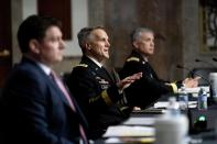 Special Operations Command Gen. Richard Clarke, center, accompanied by Acting Assistant Secretary Of Defense For Special Operations And Low-Intensity Conflict Christopher Maier, left, and U.S. Cyber Command Commander, National Security Agency Director and Central Security Service Chief, Gen. Paul Nakasone, right, speaks at a hearing to examine United States Special Operations Command and United States Cyber Command in review of the Defense Authorization Request for fiscal year 2022 and the Future Years Defense Program, on Capitol Hill, Thursday, March 25, 2021, in Washington. (AP Photo/Andrew Harnik, Pool)