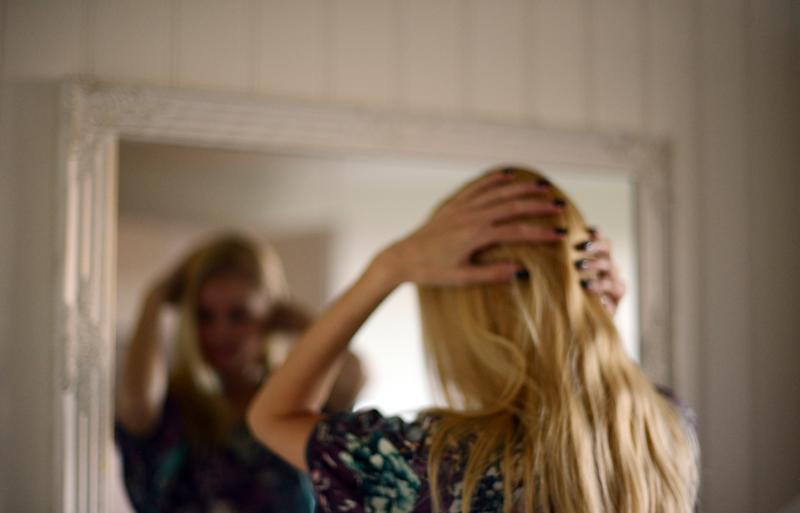 Woman looks in mirror symbolising body image disorder eating disorder