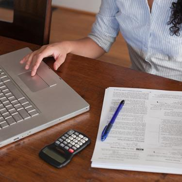Woman-working-on-computer-with-tax-docs-and-calculator_web