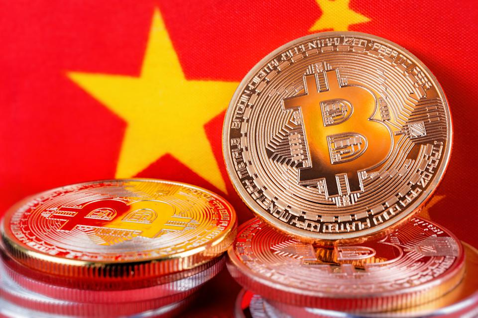 Montreal, 7 May 2018: Bitcoin real coins over chinese flag fabric