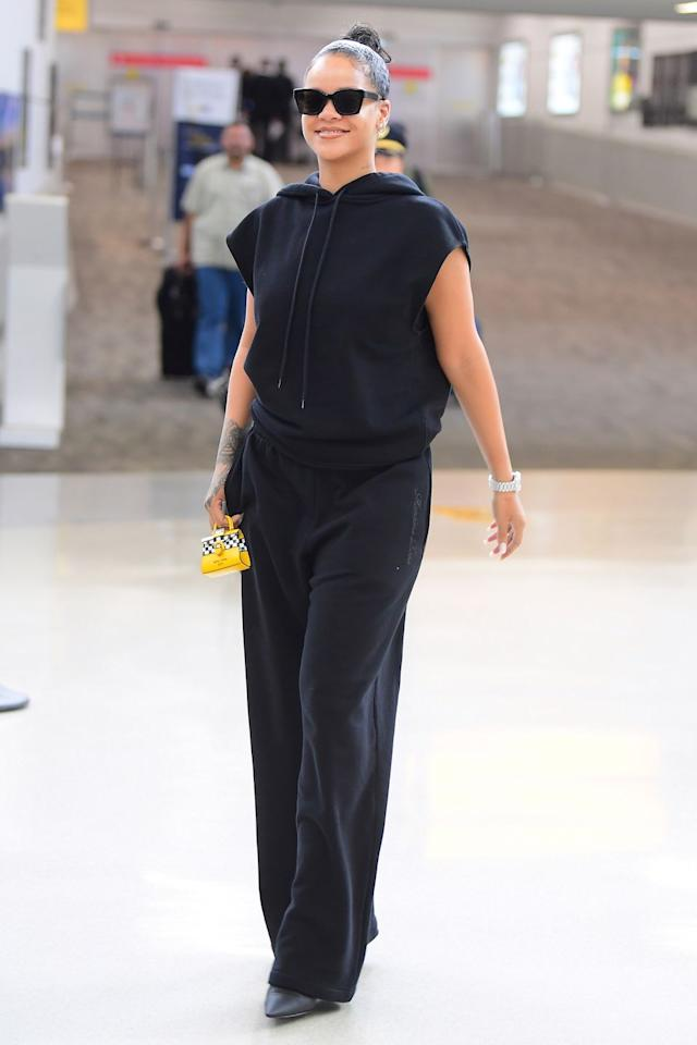 "<p>In a black sleeveless hoodie, sweat pants, pointed-toe shoes, sunglasses, and a mini taxi-print handbag by <a href=""https://www.barneys.com/designer/delvaux/N-a8kard"" target=""_blank"">Delvaux</a> at New York's JFK airport. </p>"