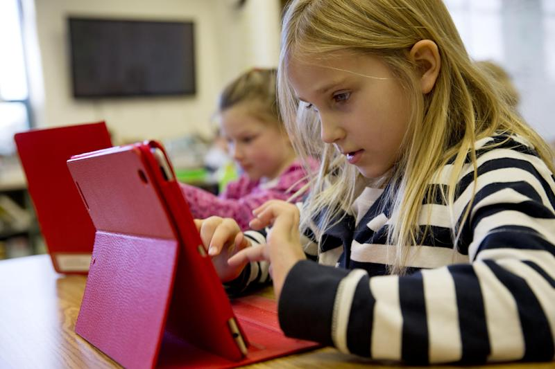 This photo taken Nov. 25, 2013 shows Ella Russell, 7, working on an e-book on an iPad during her second grade class at Jamestown Elementary School in Arlington, Va. Needed to keep a school building running these days: Water, electricity _ and broadband. Interactive digital learning on laptops and tablets is, in many cases, replacing traditional textbooks. Students are taking computer-based tests instead of fill-in-the bubble exams. Teachers are accessing far-off resources for lessons. (AP Photo/Jacquelyn Martin)