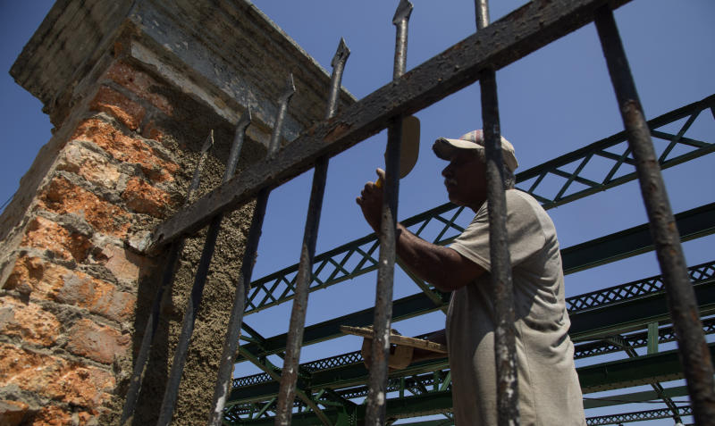 Railroad worker Norberto Rosales repairs a gate at the central train station in Havana, Cuba, Wednesday, May 22, 2019. Workers have been restoring Havana's main rail terminal, an eclectic structure built in 1912, with four floors and a mezzanine, for over 10 years. (AP Photo/Ismael Francisco)