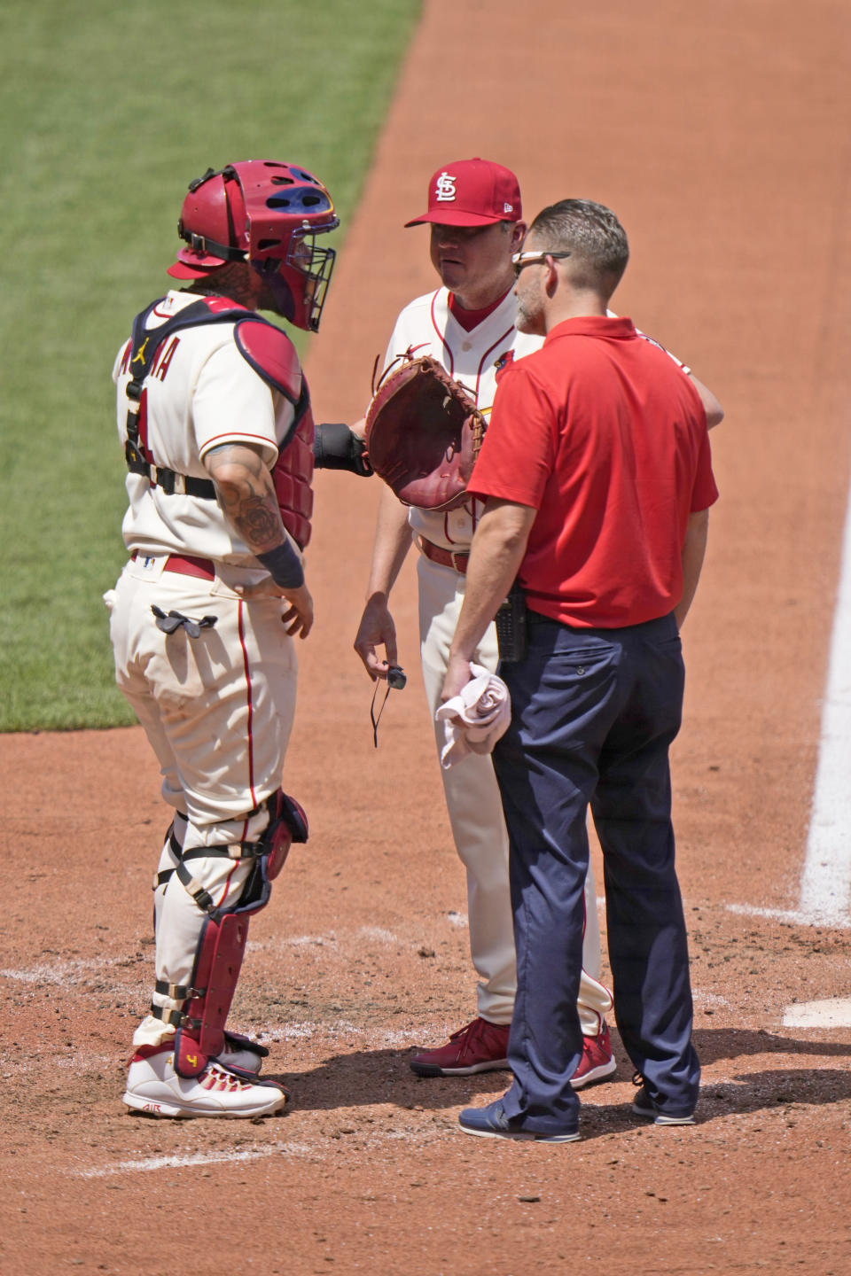 St. Louis Cardinals catcher Yadier Molina, left, talks with manager Mike Shildt and trainer Adam Olsen after being injured during the fourth inning of a baseball game against the Cincinnati Reds Saturday, June 5, 2021, in St. Louis. (AP Photo/Jeff Roberson)