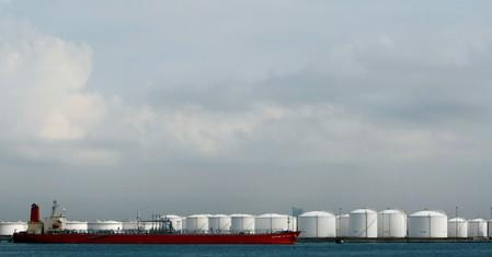 FILE PHOTO: Ship is moored near storage tanks at oil refinery off coast of Singapore