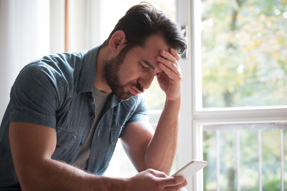 Worried man watching smartphone and waiting message